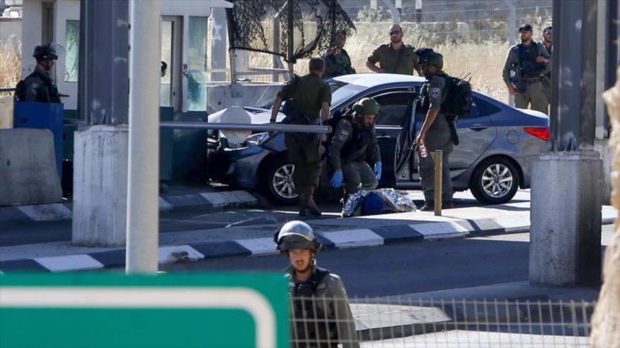 Soldados israelíes retienen el cuerpo del joven palestino Ahmad Erekat, a quien asesinaron a tiros en Cisjordania ocupada, 23 de junio de 2020. (Foto: AFP)
