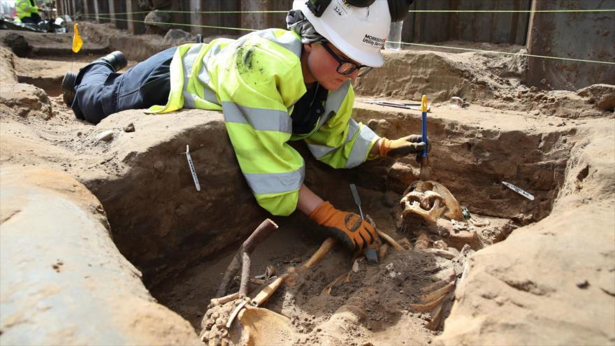 Una arqueóloga trabaja sobre restos exhumados de un cadáver encontrado en un cementerio situado en Edimburgo (Escocia), que según se cree data de la época medieval.