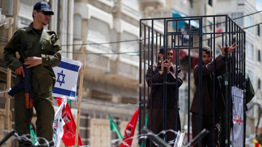 Un grupo de artistas protagonizan el sufrimiento de los prisioneros palestinos en una manifestación en la Franja de Gaza.
