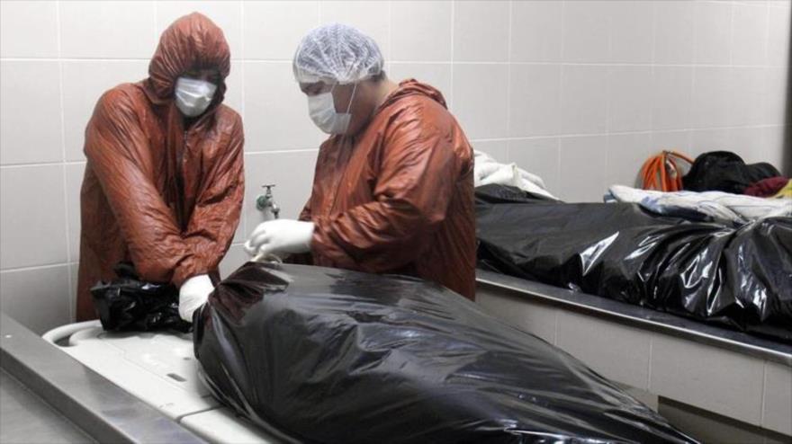 Trabajadores envuelven un cuerpo en la morgue del Hospital Pampa de La Isla, Santa Cruz, Bolivia, 12 de julio de 2020. (Foto: EFE)