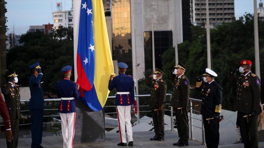 El ministro de Defensa venezolano junto con otros militares y funcionarios del país izan la bandera de Venezuela en conmemoración del natalicio de Simón Bolívar.