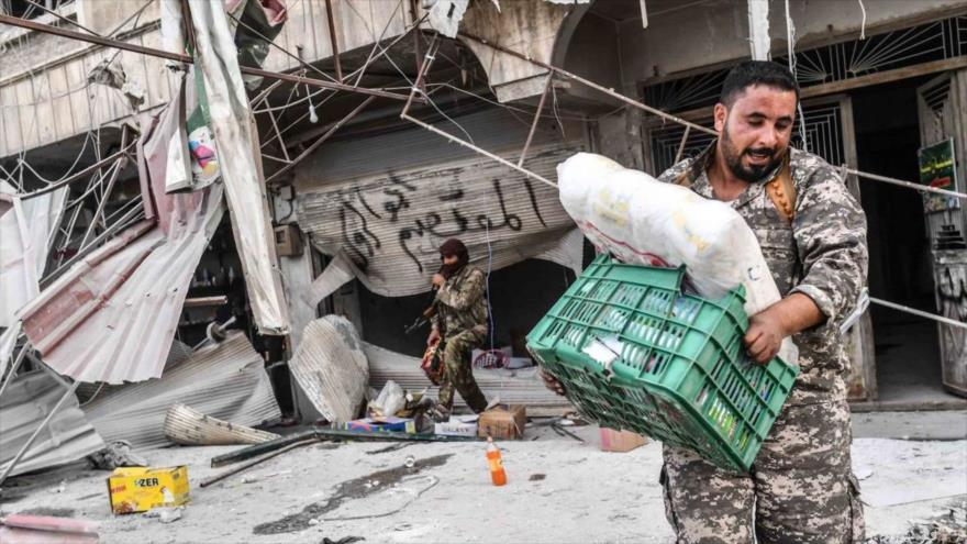 Milicianos armados saquean las tiendas en la región de Afrin, situada en el norte de la provincia siria de Alepo.