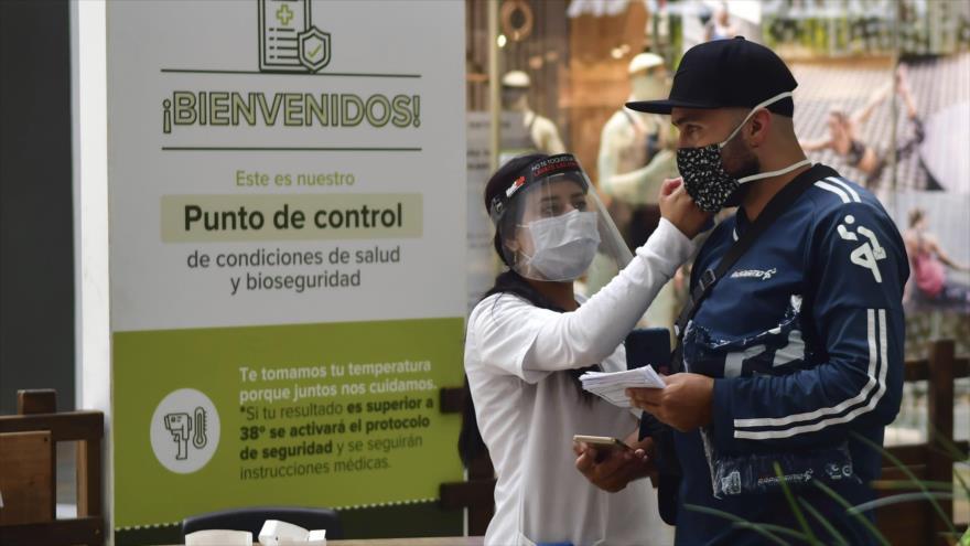 Una enfermera mide la temperatura corporal de un ciudadano en un centro comercial, en Medellín, sureste de Colombia. 9 de junio de 2020. (Foto: The Associated Press)