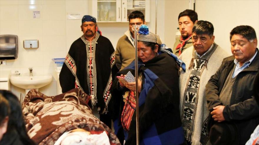 Varios miembros de la comunidad mapuche de Chile, perteneciente a la comuna de Ercilla, junto a un enfermo en un hospital comarcal.