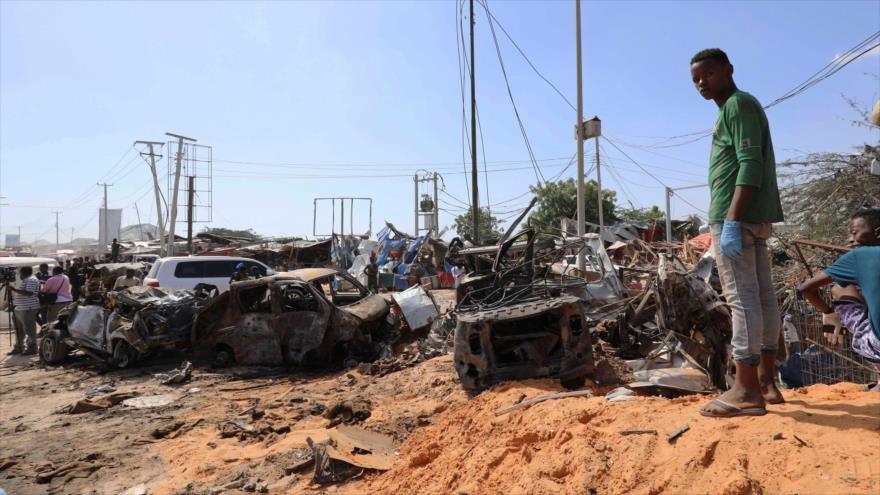 Un hombre somalí se encuentra en la escena de la explosión de un coche bomba en Mogadiscio, la capital.