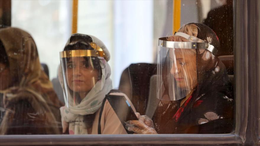 Pasajeros llevan escudos de plástico transparente en un autobús para protegerse ante COVID-19, Teherán, capital iraní, 22 de julio de 2020. (Foto: AFP)