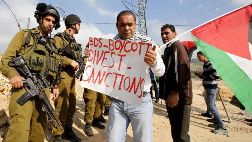 Un palestino lleva una pancarta en la que pide el boicot contra el régimen de Israel durante una protesta en la ocupada Cisjordania.