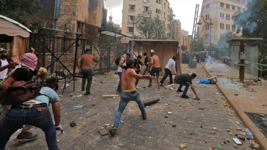 Manifestantes arrojan piedras a los agentes de la policía en una protesta en Beirut, capital de El Líbano, 8 de agosto de 2020. (Foto: AFP)