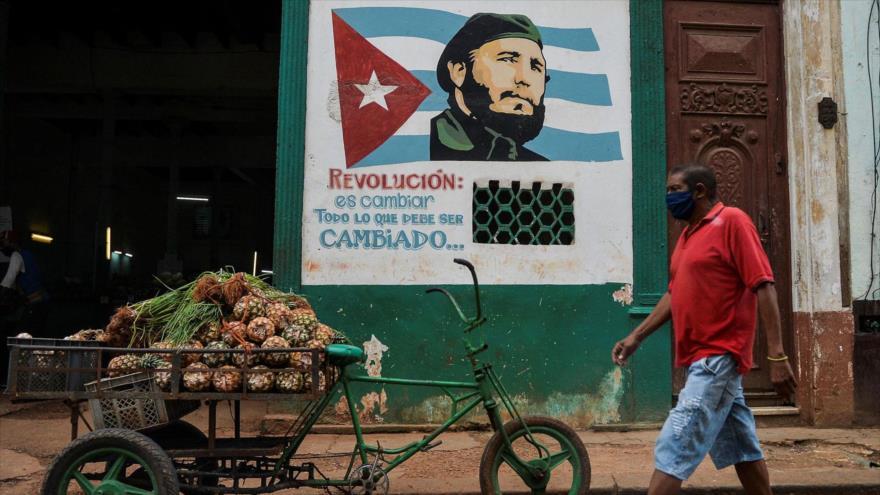 Un hombre cubano con mascarilla para evitar el contagio de la COVID-19, pasa junto a una imagen del difunto líder cubano Fidel Castro.