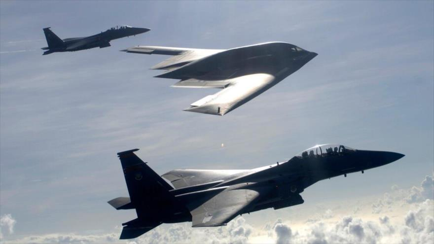 Un bombardero furtivo B-2 escoltado por dos cazas F-15 de la Fuerza Aérea estadounidense.
