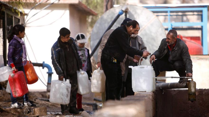 Civiles sirios hacen cola mientras llenan contenedores con agua en Al-Rabwah, en el oeste de Damasco, capital de Siria, (Foto: Reuters)
