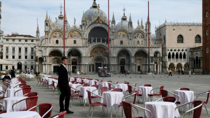 Un camarero está de pie junto a las mesas vacías de un restaurante en la Plaza de San Marcos, en Venecia, Italia, 9 de marzo de 2020. (Foto: Reuters)