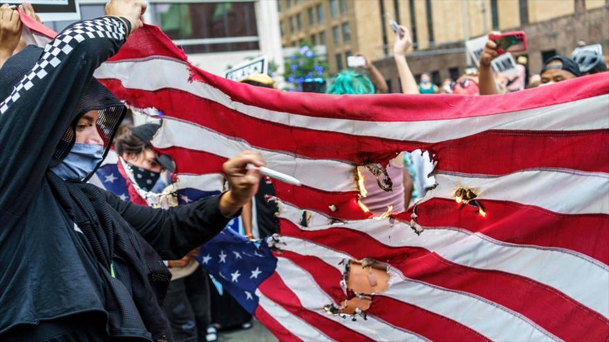 Los estadounidenses prenden fuego a una bandera de su país durante una protesta contra el racismo en Mineápolis, 24 de agosto de 2020. (Foto: AFP)