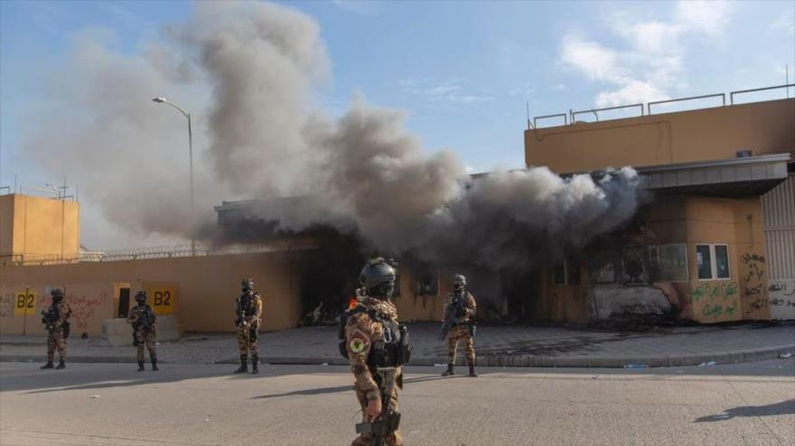 Agentes de seguridad vigilan la embajada de EE.UU. en Bagdad, capital iraquí, mientras es atacada.
