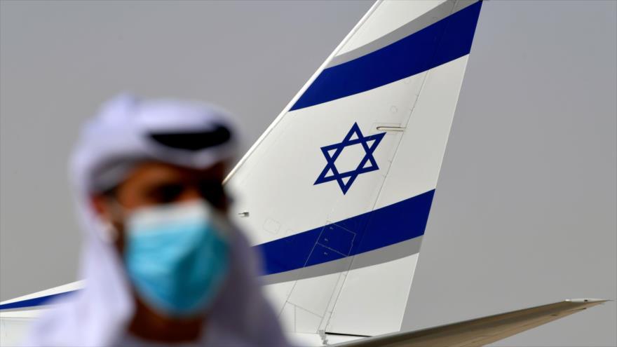 Un funcionario emiratí se encuentra cerca de un avión israelí que llegó al aeropuerto de Abu Dabi, 31 de agosto de 2020. (Foto: AFP)