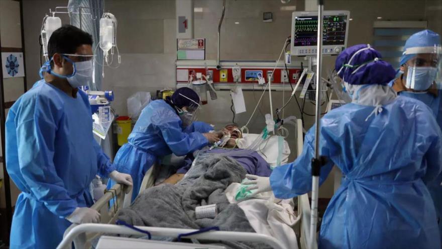 Personal médico de un hospital en Teherán, capital de Irán, intenta ayudar a una persona que ha contraído la COVID-19.
