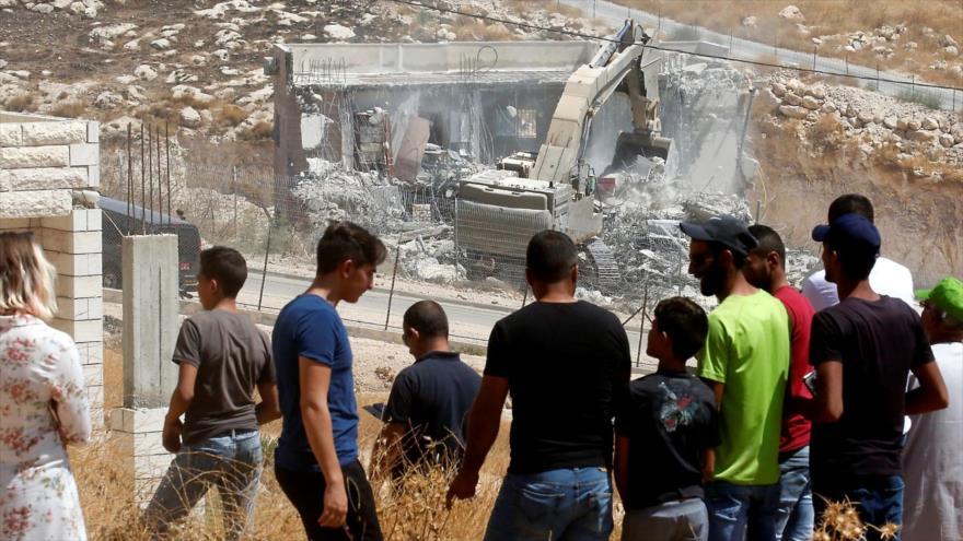 Una excavadora del ejército israelí destruye uno de los edificios palestinos en la aldea de Sur Baher, cerca de la ciudad de Al-Quds (Jerusalén).