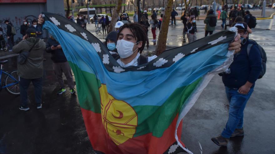 Un manifestante sostiene una bandera mapuche durante una protesta antigubernamental en la capital, Santiago, 4 de septiembre de 2020. (Foto: AFP)