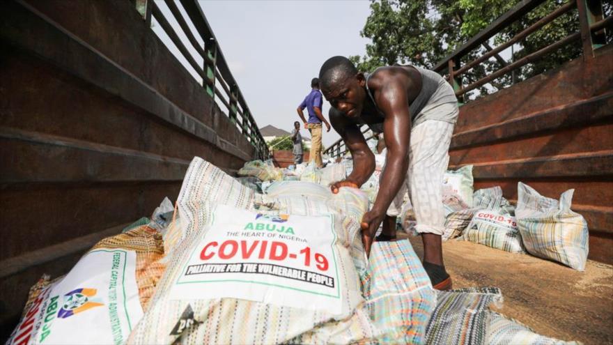 Hombres cargan sacos de arroz en un camión para distribuirlos a la gente en plena pandemia, en Abuja, Nigeria, 17 de abril de 2020. (Foto: Reuters)