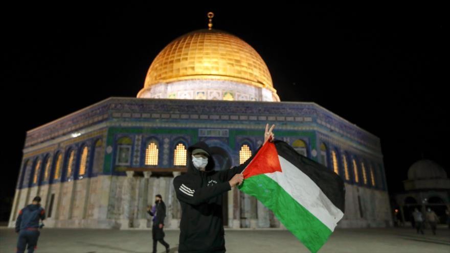 Un palestino ondea una bandera de Palestina frente a la Cúpula de la Roca, sita en el recinto de la Mezquita Al-Aqsa, 31 de mayo de 2020. (Foto: AFP)