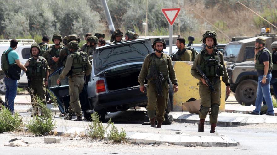 Soldados israelíes inspeccionan coche de un colono que atropelló a un palestino en la ocupada Cisjordania.