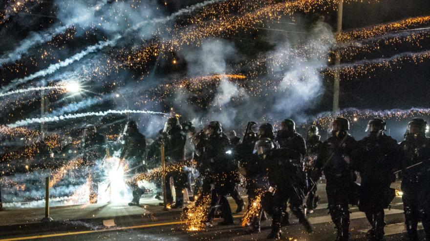 Los agentes del estado de Oregón, EE.UU., avanzan a través de gas lacrimógeno mientras dispersan una protesta antirracista, 5 de septiembre de 2020. (Foto: AFP)
