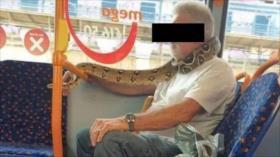 Un hombre sube al autobús con una serpiente viva como mascarilla