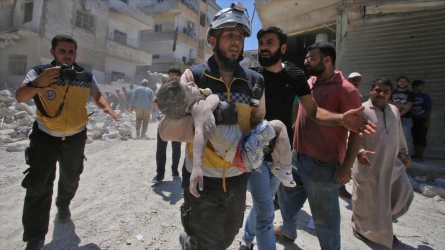 Un miembro de los llamados cascos blancos fotografiado con un niño muerto en sus brazos en una localidad en Idlib, Siria, 27 de julio de 2019. (Foto: AFP)