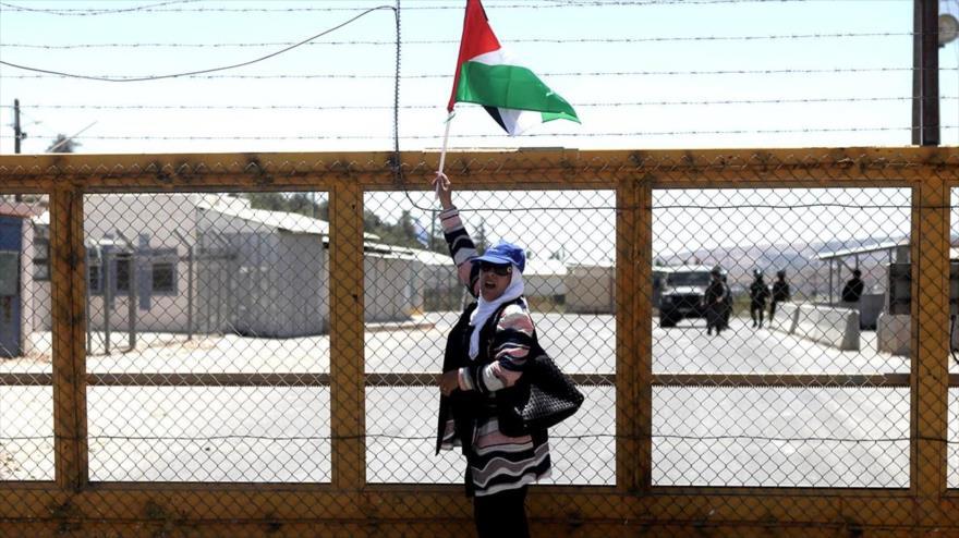 Una mujer palestina con la bandera nacional fuera de una prisión israelí en Cisjordania, para mostrar solidaridad con los prisioneros palestinos.