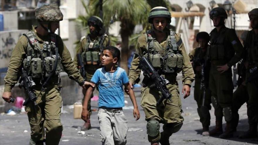 Soldados israelíes detienen a un niño en la Cisjordania ocupada.