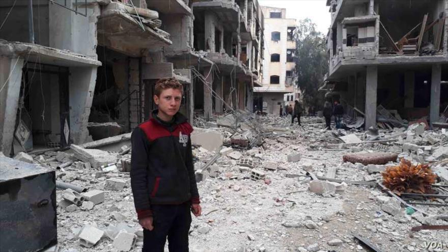 Un adolescente sirio se encuentra cerca de los escombros de un edificio en el vecindario de Guta Oriental, al este de Damasco, capital siria, 23 de febrero de 2018.