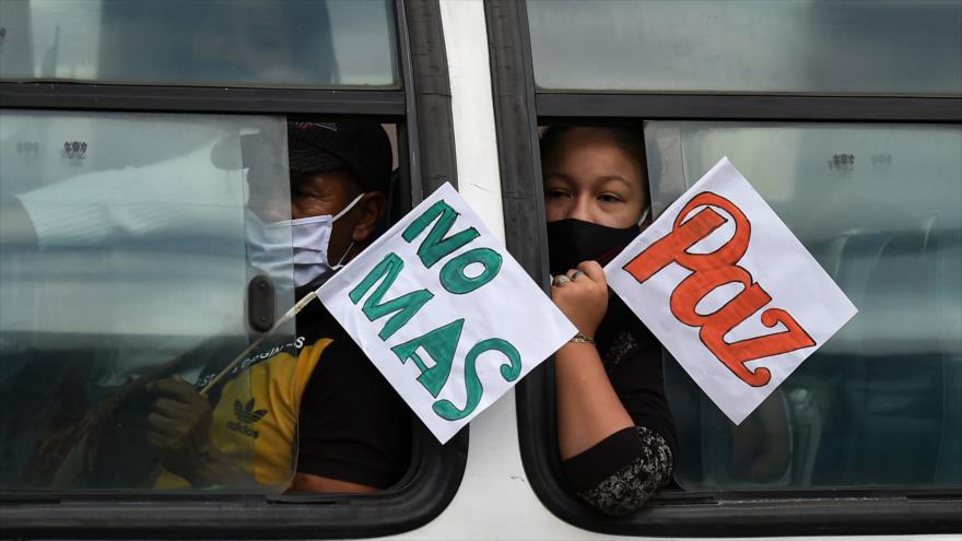 """Los colombianos, con pancartas de """"Paz"""" y """"No más"""", van al funeral de 2 exguerrilleros asesinados de las FARC, Popayan, 25 de agosto de 2020. (Foto: AFP)"""