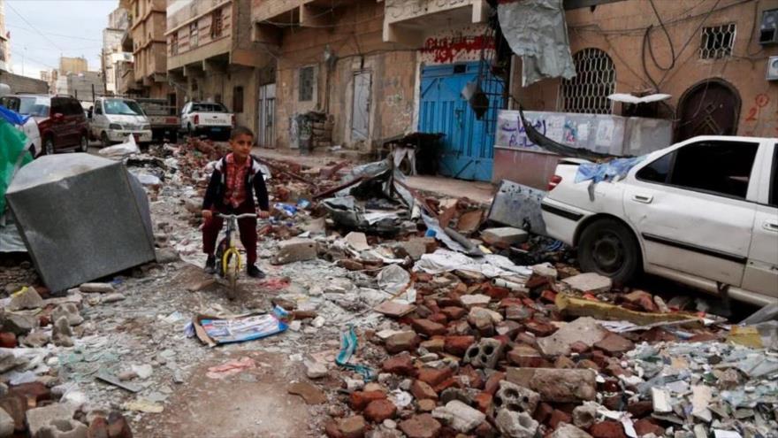 Un niño yemení va en su bicicleta tratando de esquivar los escombros de casas destruidas en un ataque aéreo de la coalición liderada por Arabia Saudí en Saná, 23 de mayo de 2019.