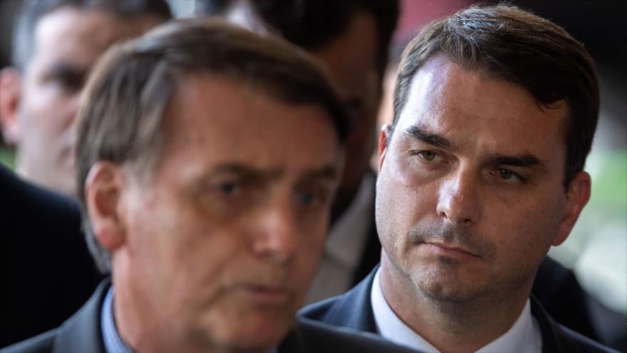 El presidente de Brasil, Jair Bolsonaro (izq.) y su hijo Flavio llegan a una conferencia de prensa en Brasilia, 28 de noviembre de 2018. (Foto: AFP)