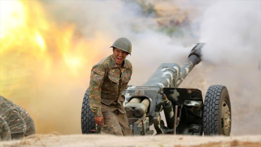 Un militar del ejército de defensa de Nagorno Karabaj dispara una pieza de artillería hacia posiciones azerbaiyanas, 28 de septiembre de 2020. (Foto: AFP)