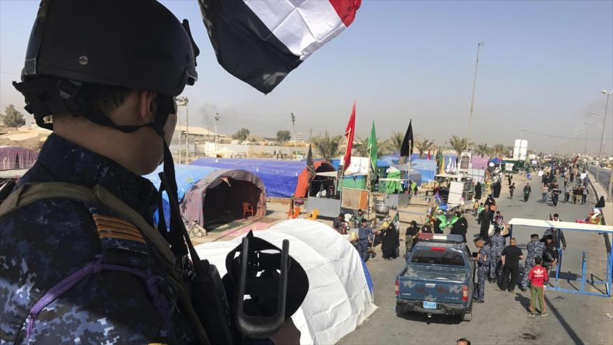 Agente de Policía hace guardia mientras los peregrinos se dirigen hacia la ciudad iraquí de Karbala antes del Día de Arbaín. (Foto: AP)