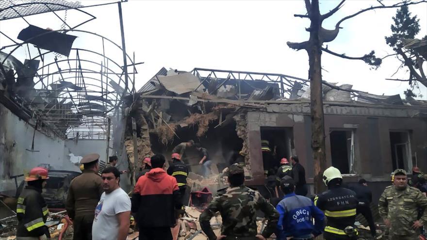 Personal de emergencia trabaja en un lugar dañado por cohetes armenios en la ciudad azerbaiyana de Ganyá, 4 de octubre de 2020. (Foto: AFP)