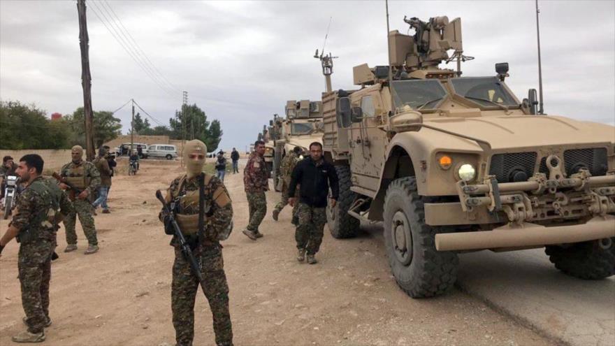 Miembros de las llamadas Fuerzas Democráticas Sirias (FDS) delante de vehículos blindados de EE.UU. en una región en el norte de Siria.