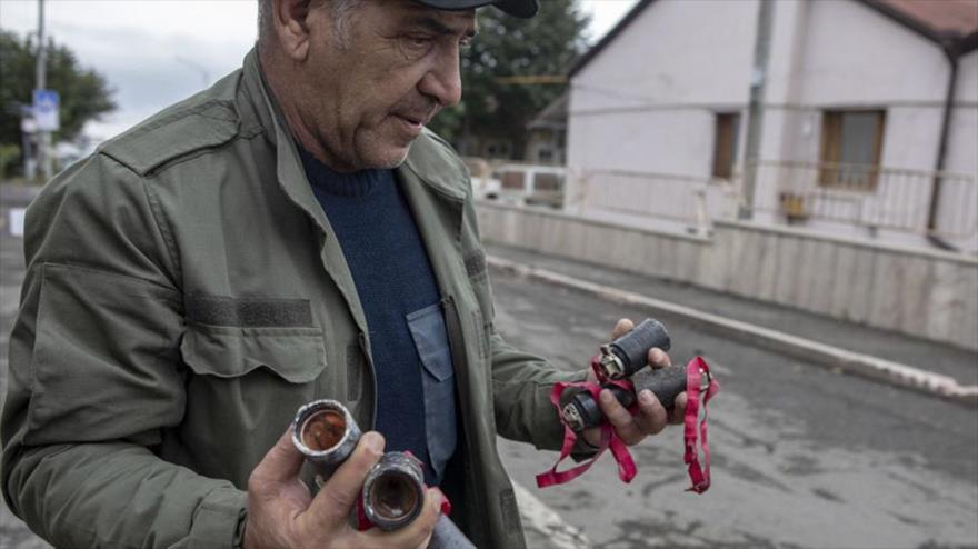 Un habitante de Stepanakert, capital de Nagorno Karabaj, sostiene varias bombas de racimo de fabricación israelí de tipo M095 DPICM en sus manos. (Foto: AI)