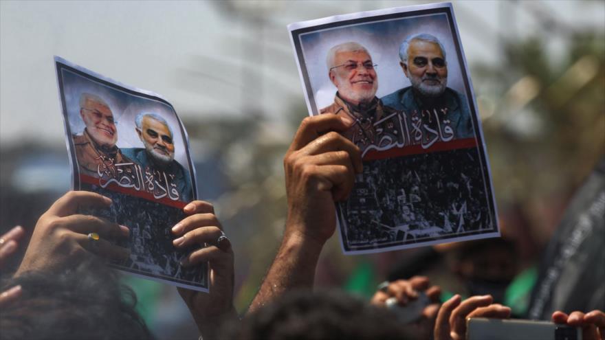 Iraquíes sostienen fotos del general iraní Qasem Soleimani y el comandante iraquí Abu Mahdi al-Muhandis, asesinados por EE.UU., 30 de agosto de 2020.