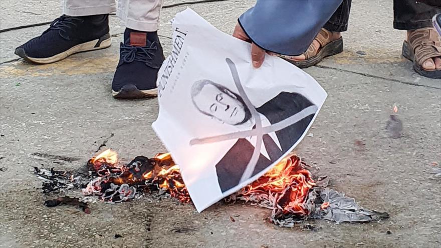 Una manifestante prende fuego a una foto del presidente francés, Emmanuel Macron, en una protesta en Trípoli, Libia, 25 de octubre de 2020. (Foto: AFP)