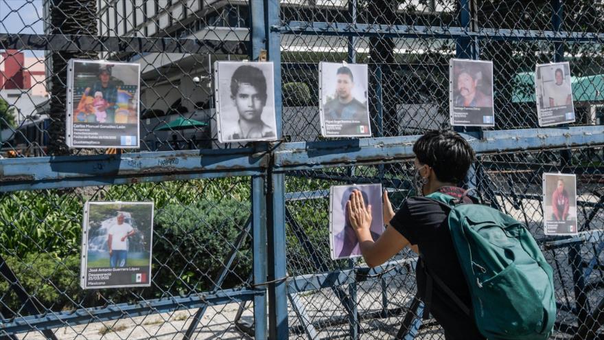 Una persona cuelga la foto de un hombre desaparecido en el aniversario de la masacre de San Fernando, Ciudad de México, 22 de agosto de 2020.