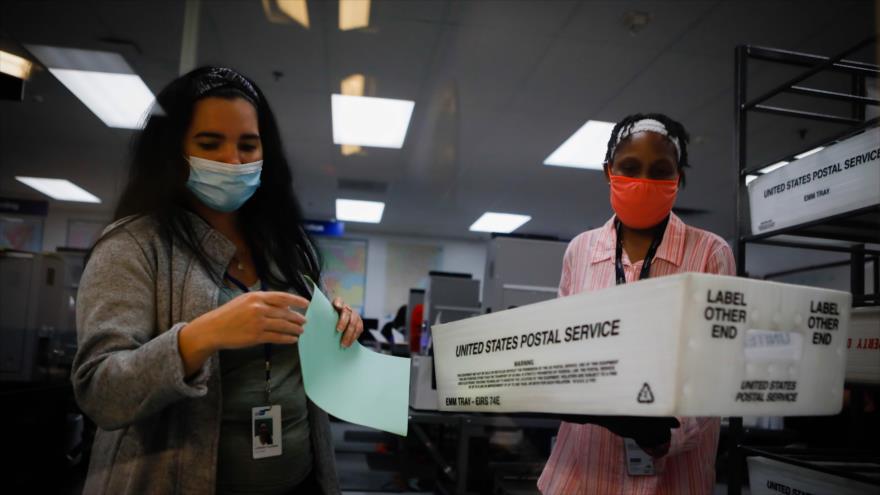 Dos trabajadores electorales de EE.UU. durante el proceso de escaneo de boletas de votación por correo en Miami, Florida, 19 de octubre de 2020. (Foto: AFP)