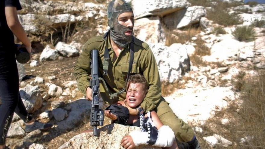 Soldado israelí detiene a un palestino en la ocupada Cisjordania.
