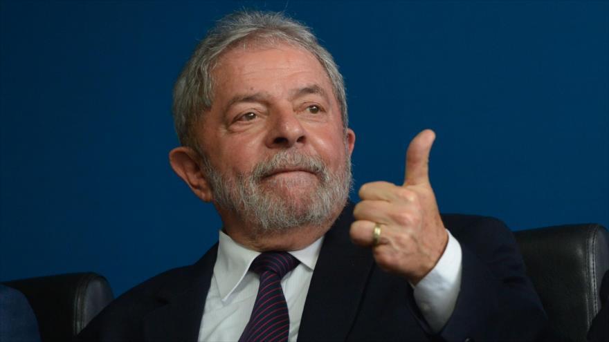 El expresidente de Brasil Luiz Inácio Lula da Silva levanta su pulgar en señal de victoria en una reunión.