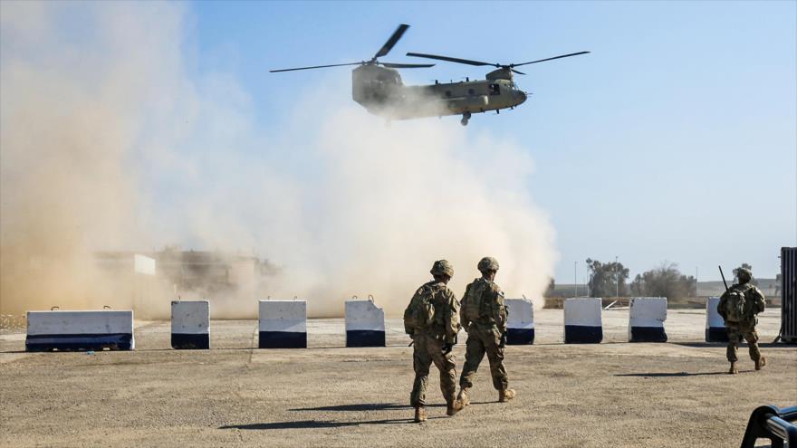 Tropas estadounidenses caminan mientras un helicóptero C-47 Chinook sobrevuela un sitio en la provincia iraquí de Mosul. (Foto: AFP)