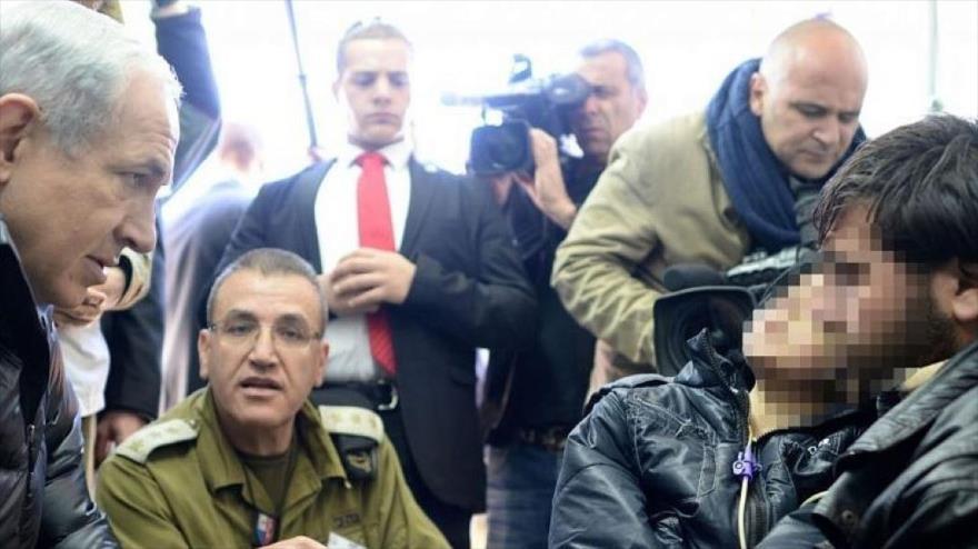 El premier israelí, Benjamín Netanyahu, visita a un grupo de opositores heridos en un hospital de campaña en el norte de Israel, 18 de febrero de 2014.