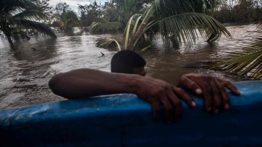Un hombre se aferra a una canoa en un área inundada después del paso del huracán Iota en Puerto Cabezas, Nicaragua, 18 de noviembre de 2020.