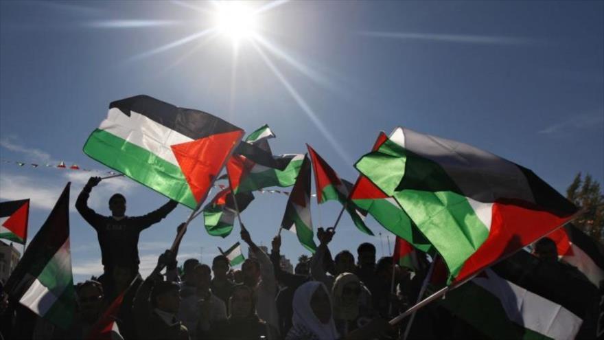 Palestinos ondean su bandera en una marcha.