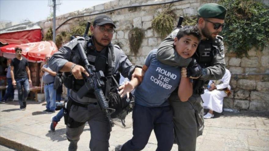 Soldados israelíes arrestan a un menor palestino en la entrada principal al complejo de la Mezquita Al-Aqsa, en Al-Quds (Jeruslaén).